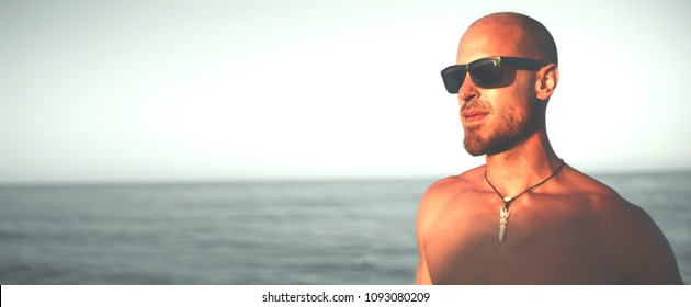 Tanned sexy man seaside. Fit male close up banner copyspace