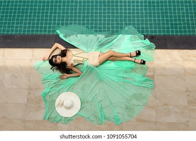 Tanned Skin Woman in Green Fashion Evening Gown Dress Lie along Edge of Swimming Pool, Top View from Above, Happy Perfect Holiday Vacation Summer big hat sunglasses high heels, Copy Space Text Logo