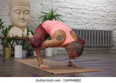 tanned skinhead woman with ethnic tattoos in yoga crane pose - bakasana