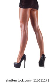 Tanned slender female legs in high heels isolated on white background