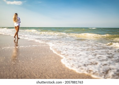 A tanned slender girl in a bluish swimsuit and a white light shirt, enjoys a warm sunny summer on the coast of a raging blue sea