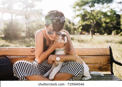 Tanned smiling lady in elegant wristwatch embracing beagle dog during rest in park at morning. Charming woman in sunglasses playing with cute pet on summer weekend.