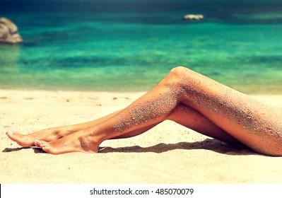 Tanned well-groomed feet amid tropical turquoise sea . Pedicure and foot Spa .