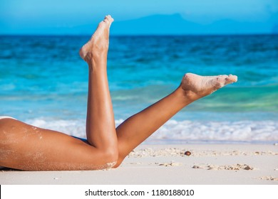 Tanned woman in bikini laying in beach, view on legs, blue sea water in background