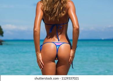 Tanned woman body in bikini, blue sea water in background