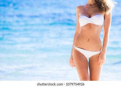 Tanned woman body in white bikini, blue sea water in background