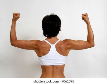 A tanned woman flexing her arm muscles