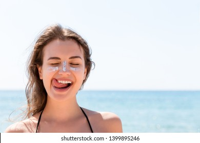 Tanned woman protects her face with sun cream from sunburn at the beach.