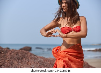 Tanned woman in red swimsuit and pareo in shape of skirt resting on beach by ocean. Young girl shows fingers sign heart, loves holidays and sea. Free traveler enjoying beautiful nature, perfect view.