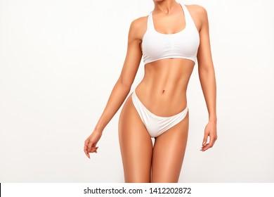 Gegerbte Frau in oberer Form, perfekte Körperform. Teile für Frauenkörper in Unterwäsche, Studioaufnahme.