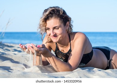 tanned young attractive woman with curly hair in black swimsuit on the beach, keeping sand in palms and sifting it through her fingers