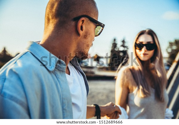 Tanned young caucasian couple, modern lovestory in film grain effect and vintage style. Sunset. Walking on the city's street, confident and happy, summer. Honeymoon concept. Toned in teal orange.
