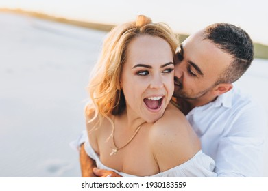 A tanned young Caucasian guy kisses a beautiful fun smiling with wide-open mouth blonde woman against the backdrop of the setting sun. Desert, sandy beach, rest and relaxation. Honeymoon concept.