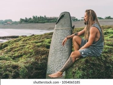 Tanned young surfer with tattoos and dreadlocks with his surfboard, sitting on the green mossy rocks near the ocean in Indonesia, Bali, Canggu, Batu Bolong beach and chilling before surfing.