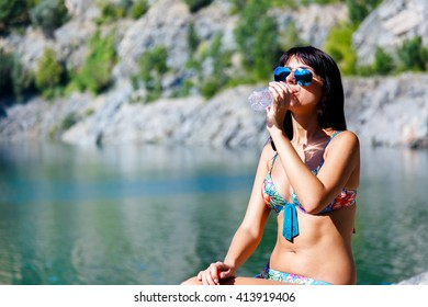 tanned young woman drinking a water on a background of mountain river at sunny summer day.