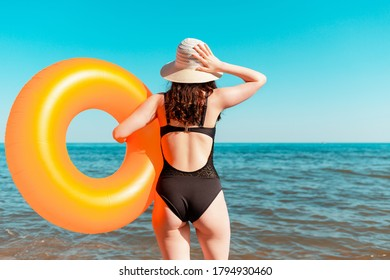Tanned young woman with an orange inflatable circle in her hands, posing against a wild beach. The view from the back. The concept of a summer holiday on the sea, traveling and swimming. Close up