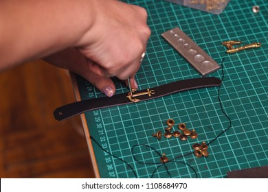 Tanner sews decorative part of anchor to leather bracelet with needle and threads. Process of working in workshop close-up.