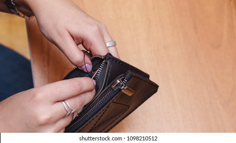 Tanner sews fastener with zipper to leather wallet. Handmade. Workflow in the workshop. Shooting close-up.