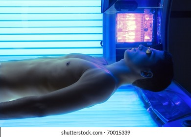 Tanning solarium young man lying real light on