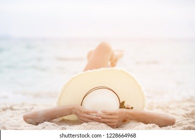 tanning suntanned young woman in bikini wearing straw hats lying on a tropical beach on white sand stretching up slender leg Blue sea in the background. Summer holiday fashion vacation travel concept.