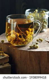 Tansy seed tea or infusion in a glass cup with flowers on wood with books nearby, herbal drink is good as anthelmintic, menstrual, kidney, rheumatism remedy , closeup, naturopathy, homeopathy concept