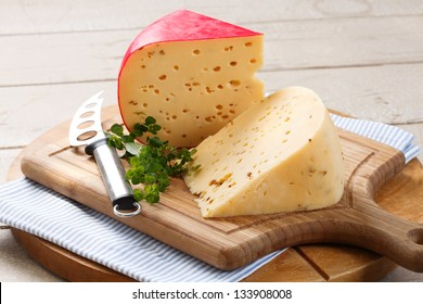 tantalizing gouda cheese and cheese knife on rustic looking wooden cutting board