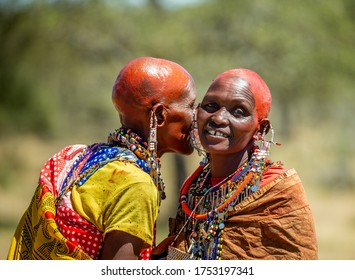 TANZANIA, EAST AFRICA - AUGUST 12, 2018: Two Masai women in traditional dress are talking to each other in the savannah. Close-up. Tanzania, East Africa, August 12, 2018.