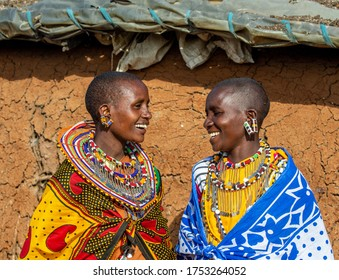 TANZANIA, EAST AFRICA - AUGUST 12, 2018: Two Masai women in traditional dress are talking to each other against the wall of a traditional house. Tanzania, East Africa, August 12, 2018.