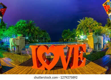 Tanzania , Zanzibar - January 2, 2019. Celebration of St. Valentine's Day on the tropical islands. luxury vacation. Inscription love and night lights on the background of exotic palms and night sky