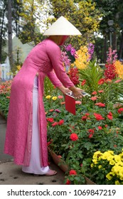"Tao Dan Park, Ho Chi Minh City, Vietnam - February 15, 2018:  A charming woman in traditional costume ""Ao Dai"" at Tao Dan Park. ""Ao dai"" is traditional clothes of Viet Nam. They were welcome a New Yea"