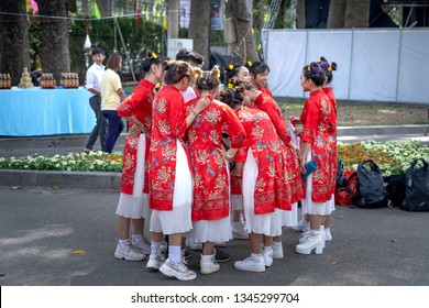 Tao Dan park, Hochiminh City, Vietnam - February 31, 2019: Beautiful young girls dressed in traditional ao dai costumes dancing in Tao Dan Park on the occasion of the year of the pig, the Lunar Year