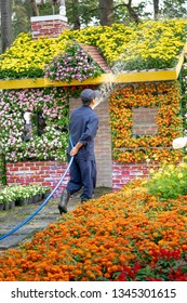 Tao Dan park, Hochiminh City, Vietnam - February 31, 2019: image of a cleaning worker taking care of a flower garden in Tao Dan Park during the Lunar New Year in 2019