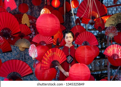 Tao Dan park, Hochiminh City, Vietnam - February 31, 2019: beautiful young girl in red traditional clothes standing in the studio with red paper fan during the Lunar New Year in 2019 at Tao Dan Park