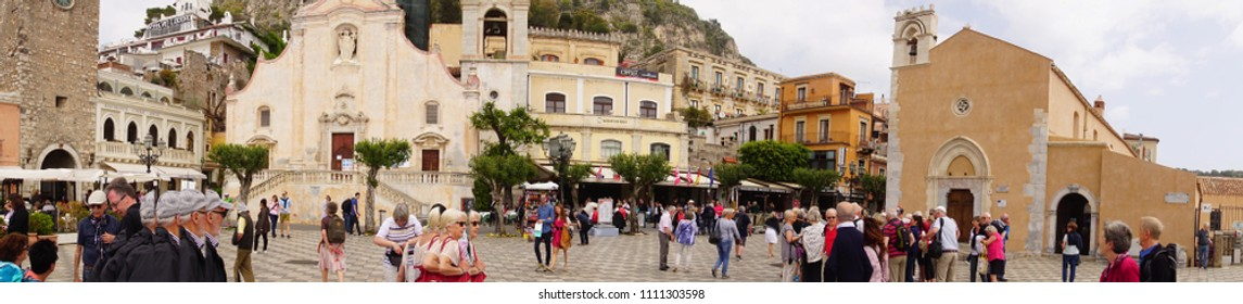 TAORMINA, ITALY- APR 18, 2018 - Panorama of tourists walking in the plaza of the hill town of Taormina Sicily, Italy