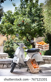 "TAORMINA, ITALY. April 3, 2015: Oranges in the box. Ancient Italian motorcycle bike ""Vespa"" parked on the street. Green orange trees in the background. Taormina city in Sicily, Italy."