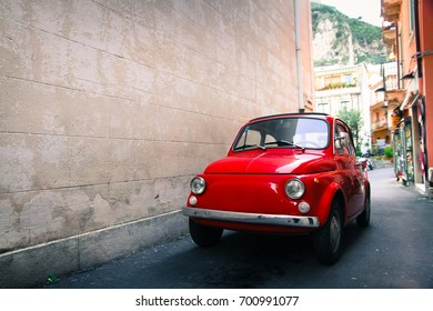 TAORMINA, ITALY - FEB 19, 2013: Red well-preserved vintage Italian classic car 500 parked in a small alley in the Sicilian city Taormina with a large empty stonewall in the left side of the frame.