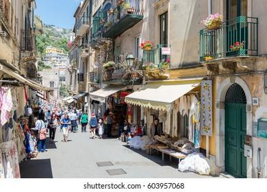 TAORMINA, ITALY - MAY 17, 2016: Tourists shopping in the street Via Teatro Creco near the Greek theatre of Taormina at the island Sicily
