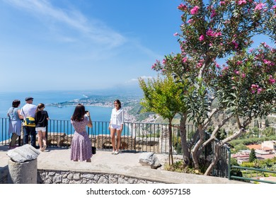 TAORMINA, ITALY - MAY 17, 2016: Tourists admiring the view and making pictures at a beautiful viewpoint near the old Greek Theatre in Taormina at the Sicilian island