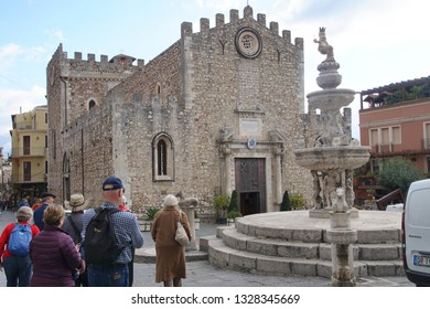 TAORMINA, ITALY- NOV 28, 2018 - Tour group and guide around a fountain in Taormina Sicily, Italy