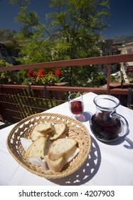 taormina italy restaurant table with red wine and crusty italian bread with view of town