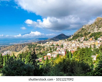 Taormina, Sicily, Italy on the Ionian Sea. The village rests on a hillside with a smoking Mount Etna in the hazy distance.