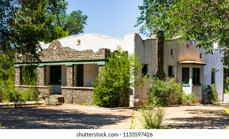 TAOS, NM, USA-8 JULY 18: A Mission Revival style, rock and stucco home stands empty on Paseo del Pueblo Norte.