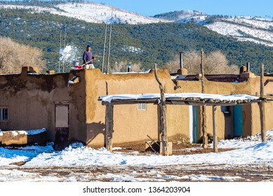 TAOS PUEBLO, NEW MEXICO / UNITED STATES - NOVEMBER 19, 2015: Unidentified man shovels snow from the roof of an adobe house in the centuries-old Native American settlement of Taos Pueblo
