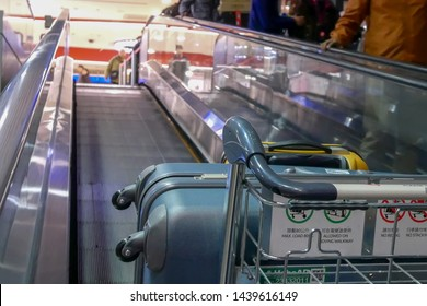 Taoyuan, Taiwan - January 25, 2019 : Motion of people pushing luggage on moving escalator inside Taoyuan international airport in Taoyuan Taiwan