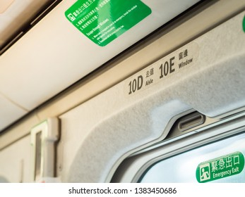 TAOYUAN, TAIWAN - March 11, 2019: Closeup overhead seat numbers in Taiwan High Speed Rail (THSR) and Emergency Exit sign with yellow sunlight through the window.