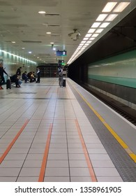 Taoyuan,Taiwan-Circa March 2019: In early morning, few people stand and wait for the high speed train on the empty platform at the station.
