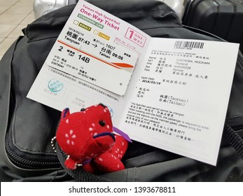 Taoyuan,Taiwan-Circa March 2019: Red bear doll sits and pretends as a passenger to read details on two sided page flipping of one way ticket provided by Taiwan High Speed Rail.