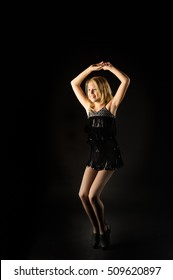 tap dancer standing in a tap pose in a black background