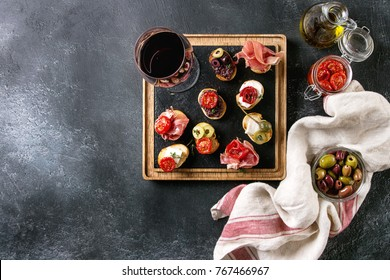 Tapas or bruschetta variety. Bread with ham prosciutto, sun dried tomatoes, olive oil, olives, pepper on slate wood serving board with glass of red wine over dark background. Top view with space