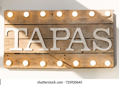 Tapas sign made of wooden planks and light bulbs on top and bottom